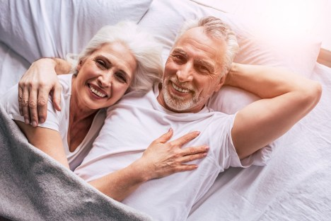older couple laying in bed together smiling.