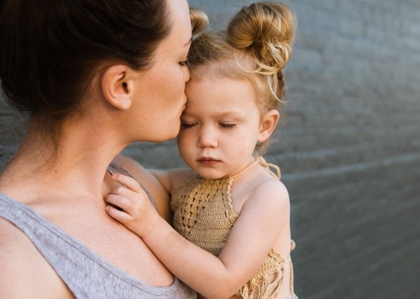 caucasian woman holding a young girl and kissing her head.