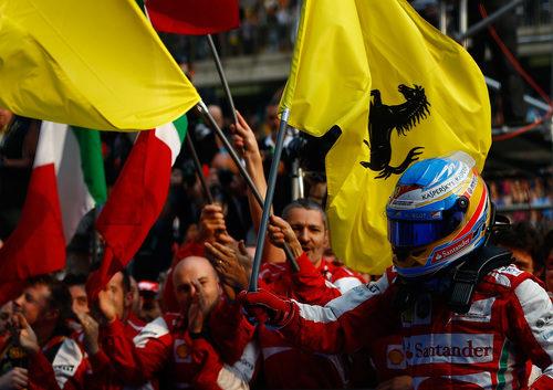 Alonso celebrando su victoria con la bandera de Ferrari