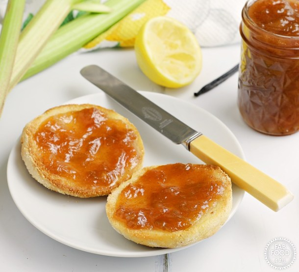 Rhubarb, Lemon and Vanilla Jam spread on a muffin with rhubarb stalks, lemon half & vanilla pod in background.