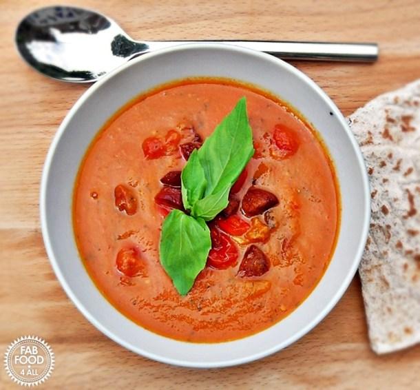 Roasted Tomato, Red Pepper & Chorizo Soup with basil leaf garnish.