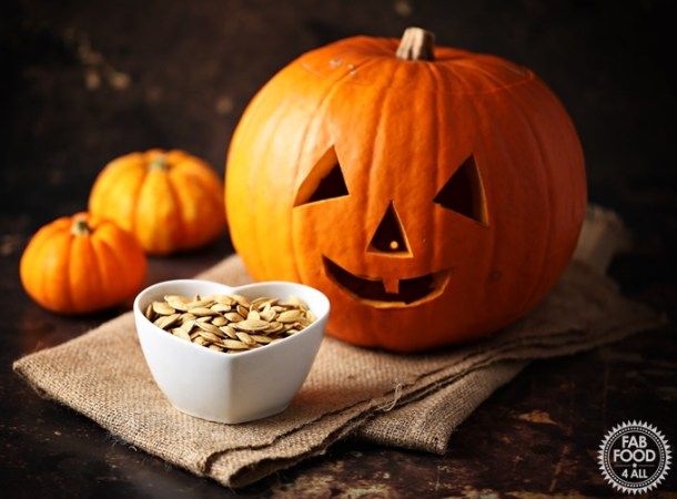 Roasted Pumpkin Seeds in a dish with Pumpkins & jack-o-lantern in the background.