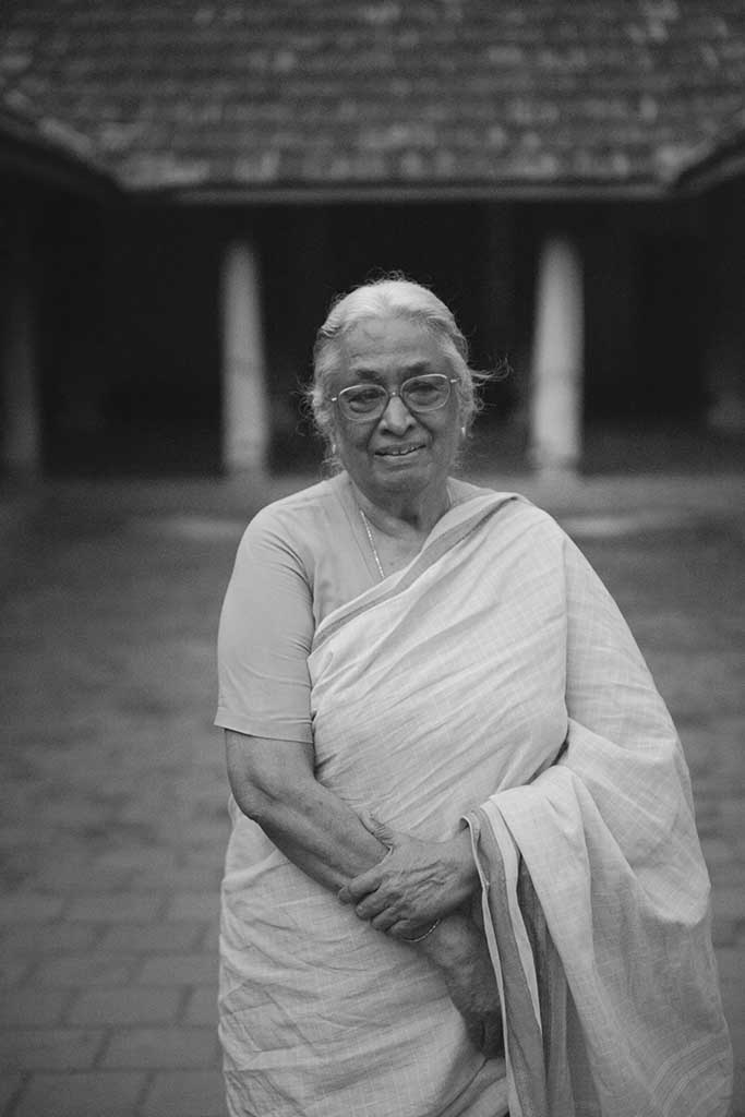 A black and white portrait of Mrs. Meenakshi Meyyappan, proprietor of The Bangala Hotel, in the courtyard of her Karaikudi home.
