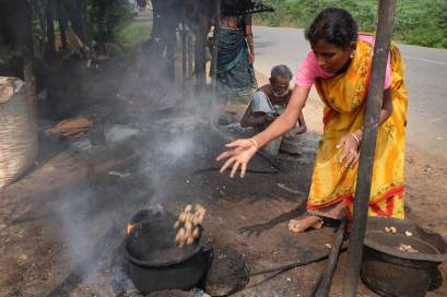 A young woman in a yellow and orange sari with a pink top is in a bent position while tossing cashews with an extended right arm into an old iron pot placed on a fire on the dirt ground.