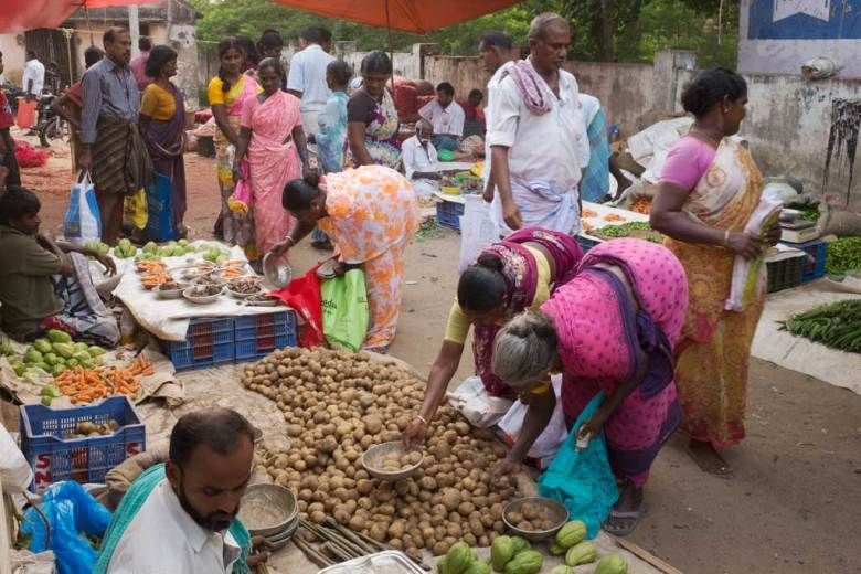 Two South Indian women wearing colourful saris, one pink, the other mauve and yellow, bend low over a large mound of russet potatoes, placing their selections in round silver bowls. Many people in the vegetable market walk around them and do their own shopping.