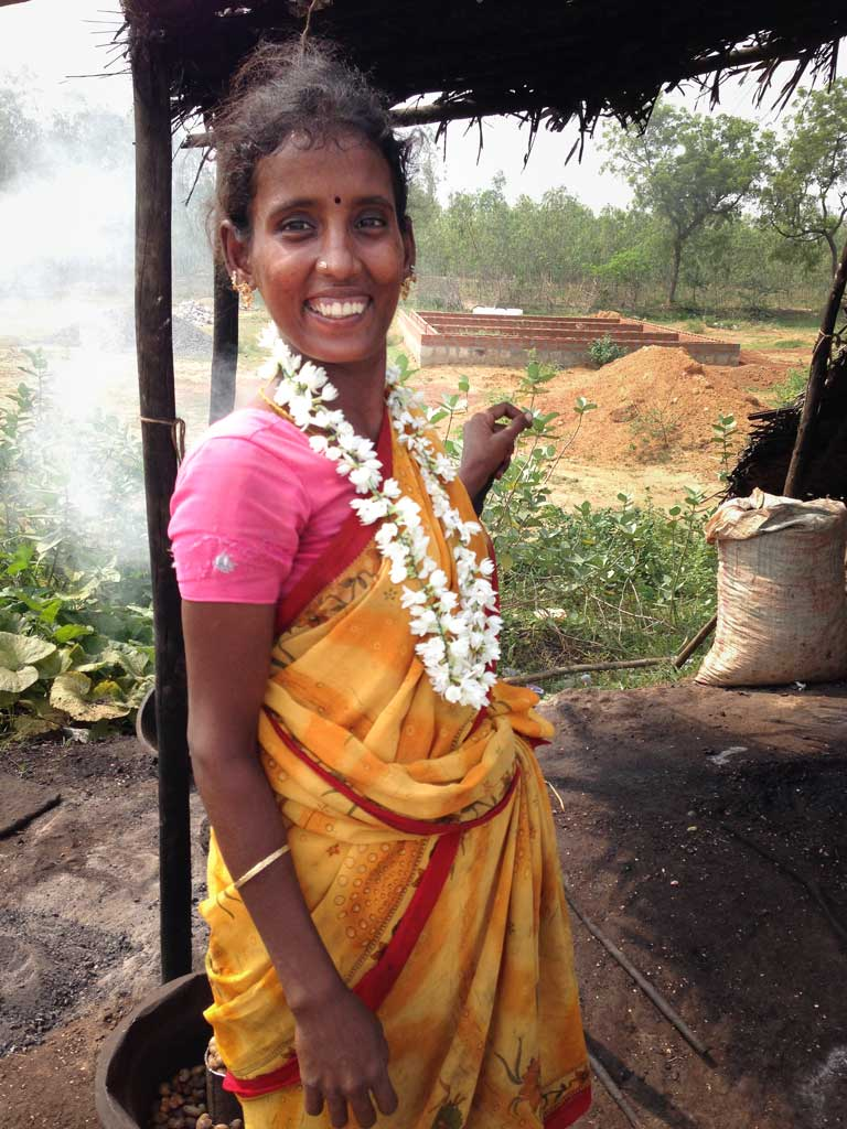 A young South Indian woman wearing a yellow and orange sari with a pink top and a necklace of jasmine smiles at the camera. Smoke from her roasting cashews rises behind her.