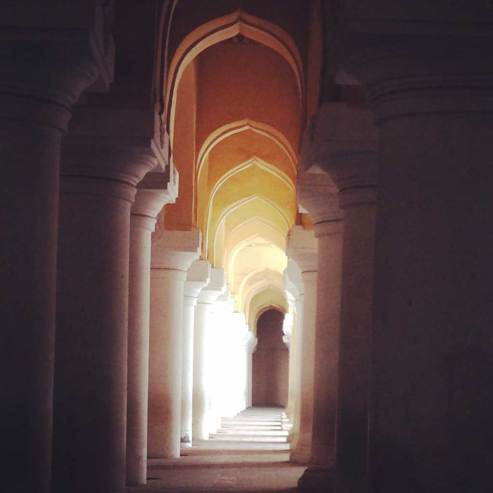 Concentric arches fade into the distance at the Nayakar Mahal Palace, Madurai. The light gradually fades as the columns appear nearer to us. The light on the arched ceiling detail changes from yellow to orange to ochre.