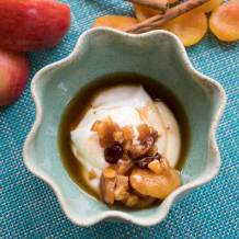Fruit compote sits atop of creamy yoghurt in a light blue bowl.