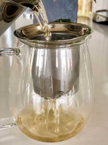 Sukku coffee is poured from the pot, through a strainer, and into a glass pot.