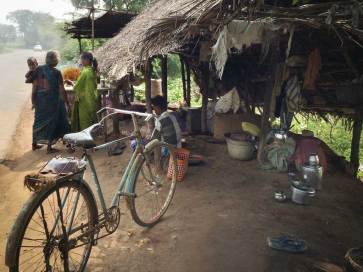 An old bicycle waits in the foreground of a thatched roofed, open-air cashew roasting operation.