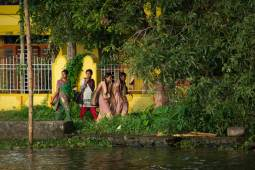 Local women walk along the verdant paths of the Kerala Backwaters.