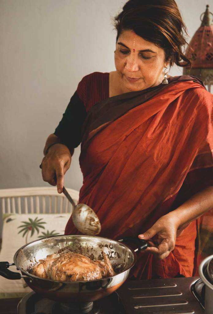 Anita wearing a burnt orange sari making poulet
