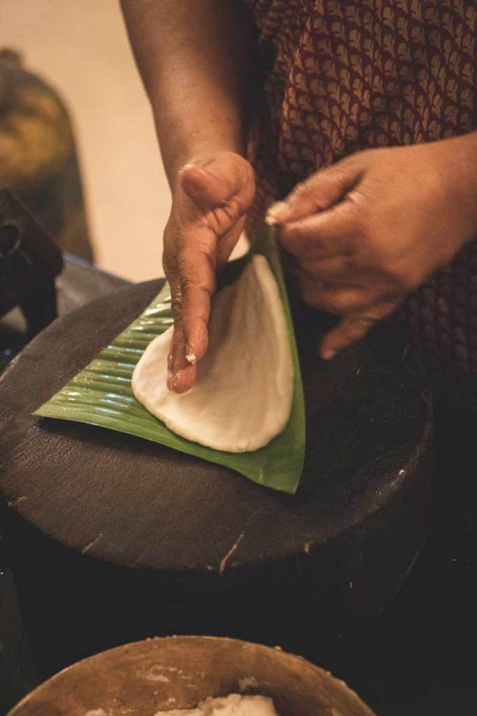 White Pathiri dough rolled out on a green banana leaf