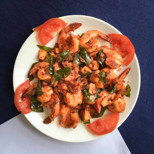 A dish of coconut prawns sits on a blue tablecloth