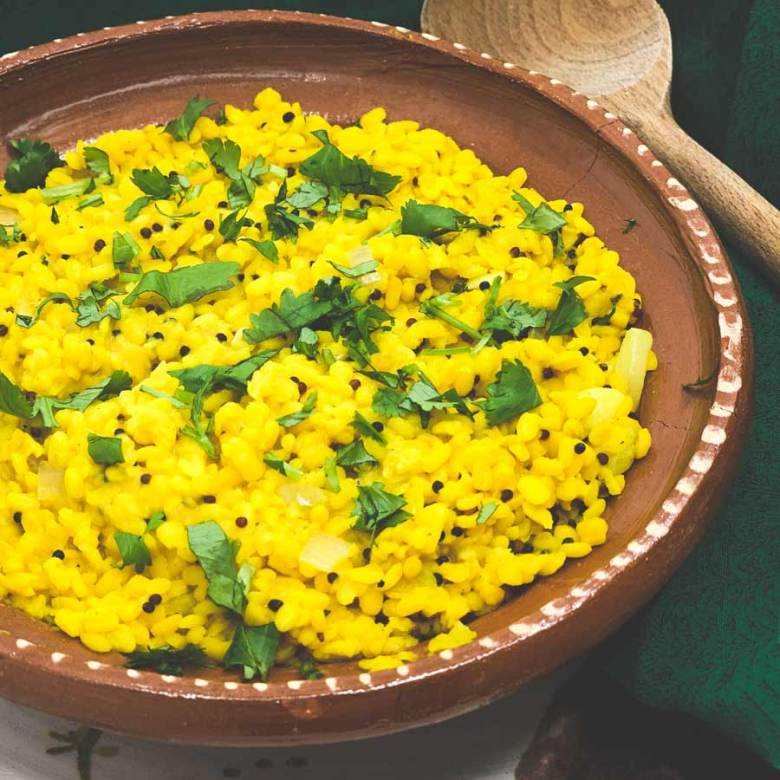 Yellow Moong Dal Curry sits in a round clay bowl.