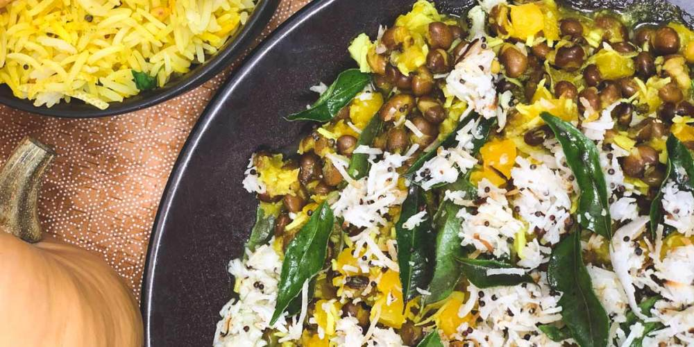 Pumpkin and Pigeon Peas with rice and curry leaves sit in a black serving bowl.