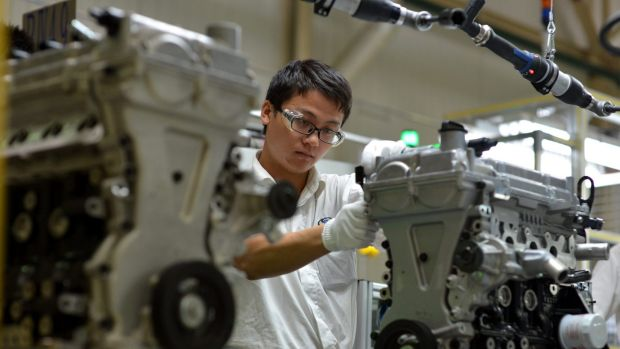 A worker assembles an engine at the General Motors plant in Wuhan, central China.