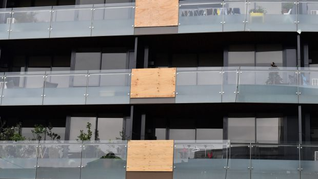 Balconies in this Melbourne apartment building have been patched up with wood following multiple glass explosions.