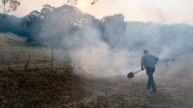 Gilman Clark, a longtime resident of Wooden Valley, takes a shovel to burning grass along a fence line next to a ...
