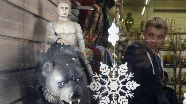 A carved figure depicting Russian President Vladimir Putin sitting on a bear displayed in a gift shop window in ...