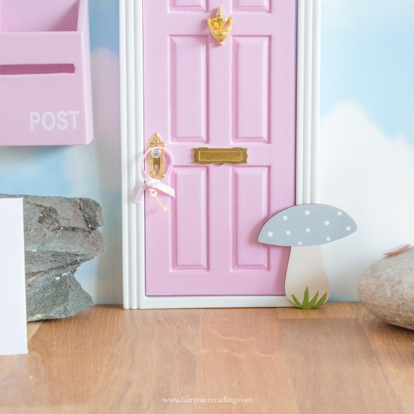 grey and pink fairy door with a toadstool