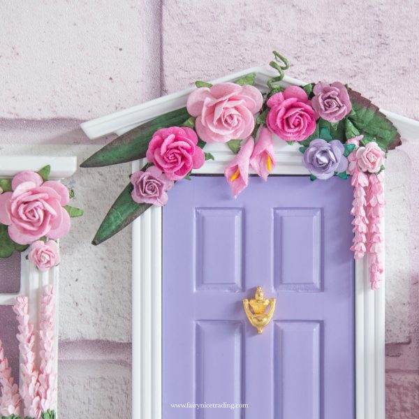 large purple fairy door with flowers