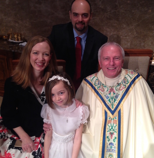 Margaret, age 7, with her parents and pastor following the Mass. First Communion today is much more a family and community experience than it once was.