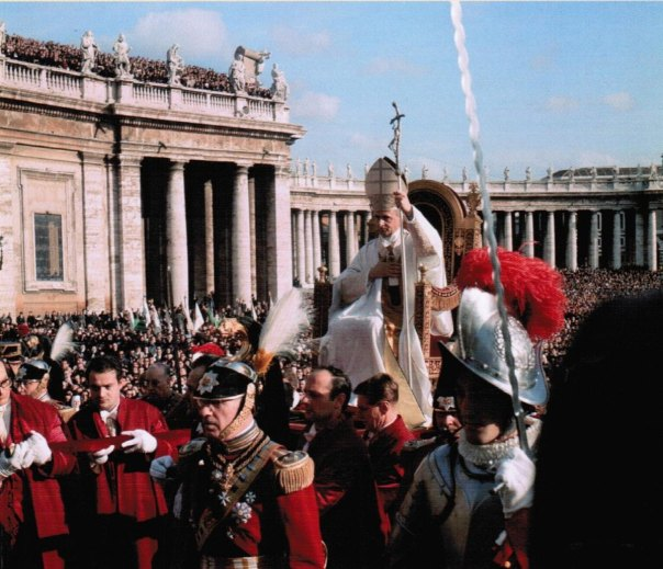 """Blessed Pope Paul VI being carried on a moveable throne surrounded by Swiss and Noble Guards. The scene, played out before an enormous crowd in St. Peter's Square is a far cry from the """"pope-mobile"""" of more recent pontiffs."""