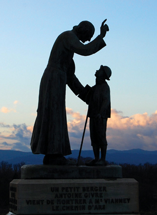 An statue outside the church depicts the elderly pastor blessing a shepherd boy.