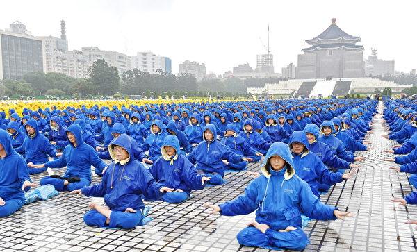 約6400名來自台灣及世界各地部分法輪功學員,11月25日齊聚在中正紀念堂排字,雖然台北雨勢不斷,但他們風雨無阻。圖為法輪功學員演煉功法。(孫湘詒/大紀元)