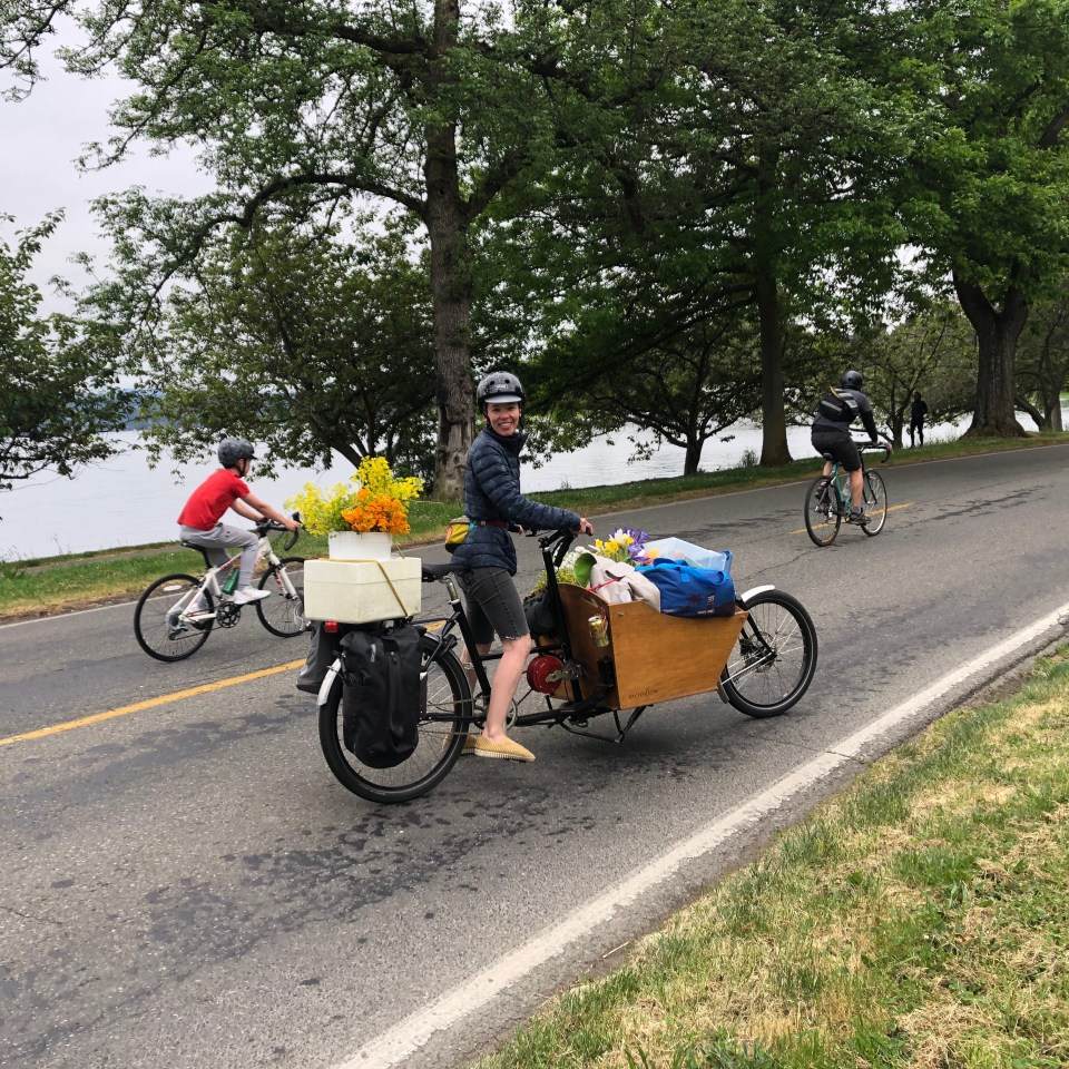 Woman posing with a cargo bike filled with bouquets of flowers and coolers filled with snacks.