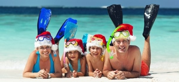 happy family with santa hats and snorkeling gear relaxing on sandy beach in front of tropical lagoon