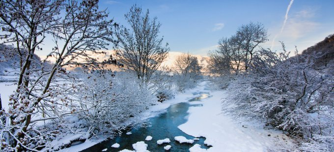 England, North West, Lake District, Keswick, Borrowdale, Stonethwaite Valley. Standing in deep snow and sub zero temperatures looking down along the frozen Derwent River in Stonethwaite Valley towards Castle Crag where the warm early morning orange sun is lighting up the mountains.