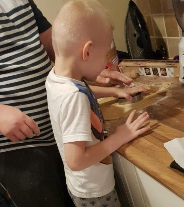 Logan cutting the dough for his Gingerbread Men Family Clan