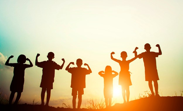 Children silhouettes showing muscles at sunset.
