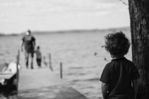 Child watches alone as adult and child walk away down a dock over water