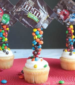 Gravity Defying M&M Cupcakes that look like a bag of m&m's being poured onto the cupcake