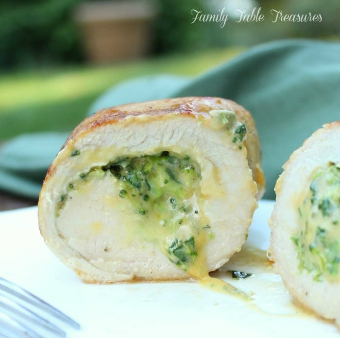 Cheesy Broccoli Stuffed Chicken Breast sliced with creamy cheese and broccoli coming out onto the plate