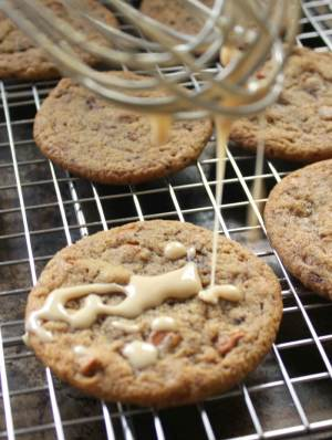 cookies on a cooling rack with a whisk covered in coffee glaze dripping onto cookies.