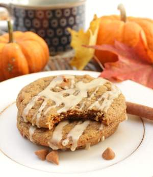Stacked Spiced Pumpkin Latte Cookies on a white plate with pumpkins, fall leaves and a coffee mug in the background
