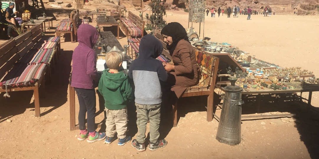 Childrens watching womens handy craft in petra Jordan