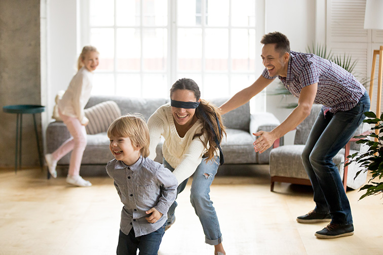 Blindfolded mother catching little son playing hide and seek at home; Courtesy of fizkes/Shutterstock