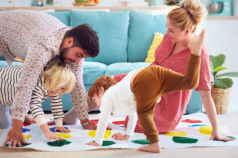 family having fun together, playing twister game at home; Courtesy of Olesia Bilkei/Shutterstock