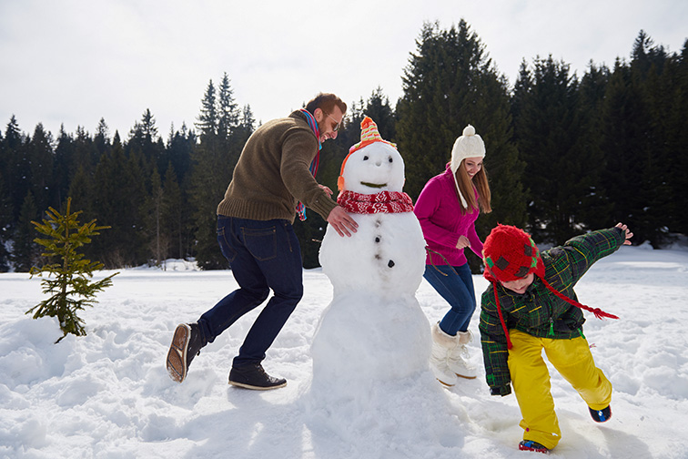 happy young family playing in fresh snow and building snowman ;Courtesy of dotshock/Shutterstock