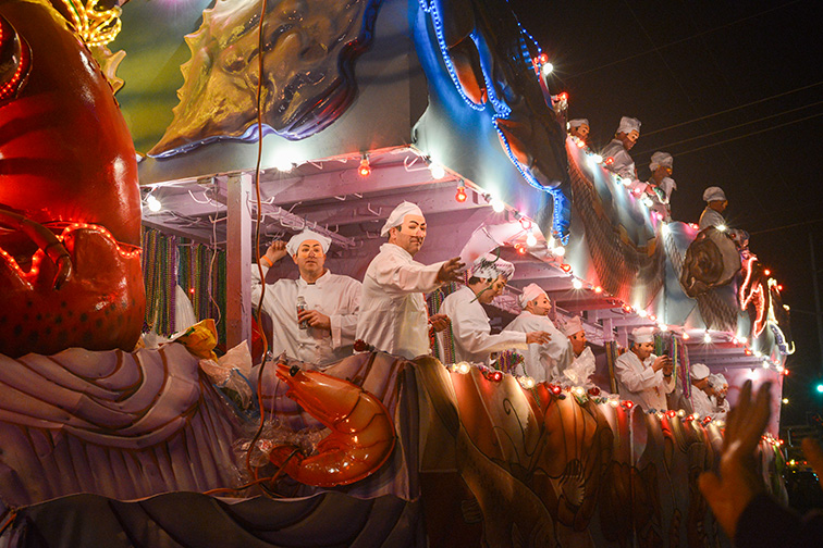 """Festively clad riders toss """"throws"""" off of a float in the Krewe of Caesar's parade in Metairie, Louisiana; Courtesy Suzanne C. Grim/Shutterstock"""
