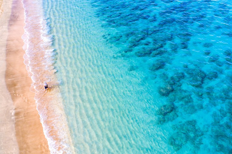 above view of beautiful Hawaiian beach on island of maui, man standing in water fishing
