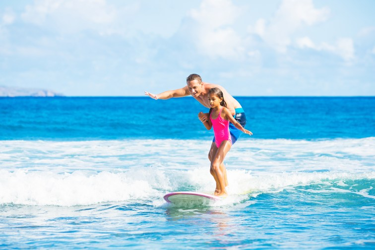 Girl in fluorescent pink bathing suit on surfboard, with adult male behind her, coaching her to surf