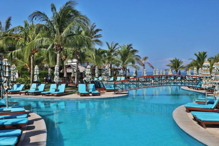 beautiful, large pool with blue chaise lounges around it, bright blue sky and palm trees