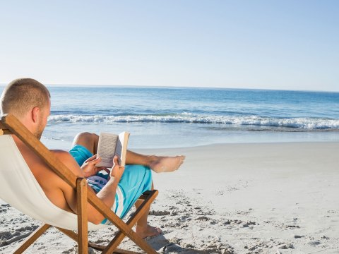 Man Reading a Book on the Beach; Courtesy of wavebreakmedia/Shutterstock.com