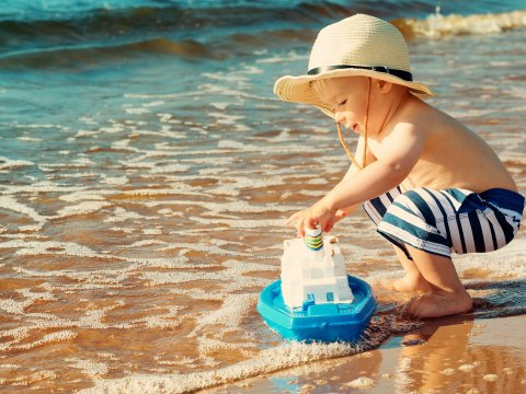 Boy Playing With Toy Boat on Beach; Courtesy of LeManna/Shutterstock.com